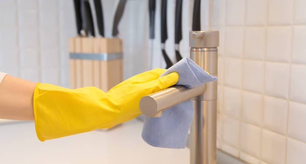 Closeup of female hand in gloves cleaning the kitchen tap